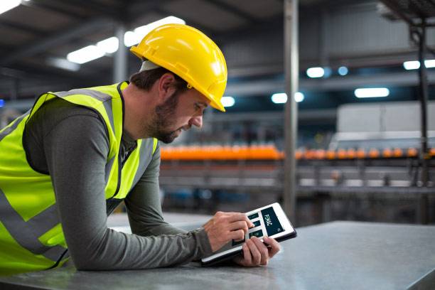 A man in a factory with PPE holding a tablet.